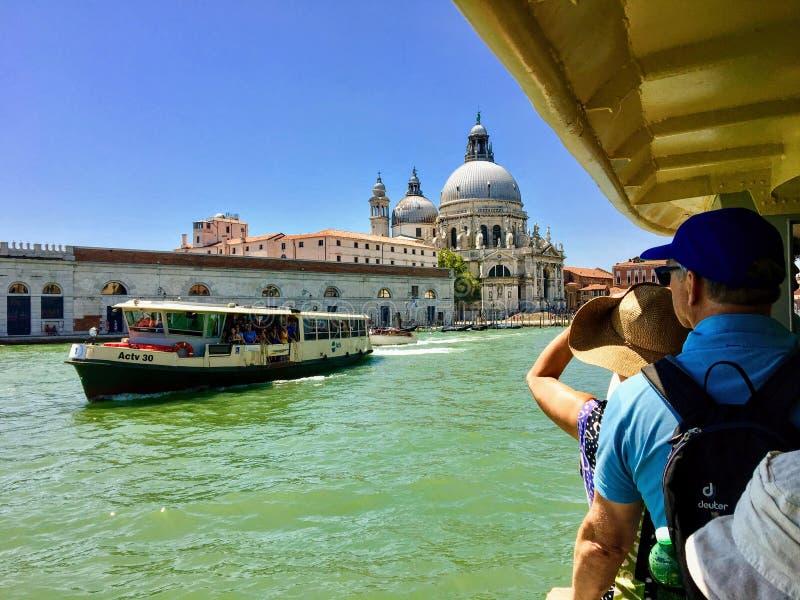 一对夫妇坐着水上出租车,在著名的威尼斯教堂圣玛利亚德拉礼塔运河拍照, 图库摄影