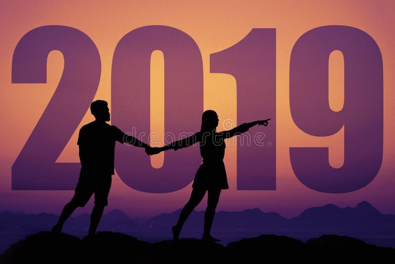 一对夫妇的剪影在爱的在日落与新年2019年 库存照片