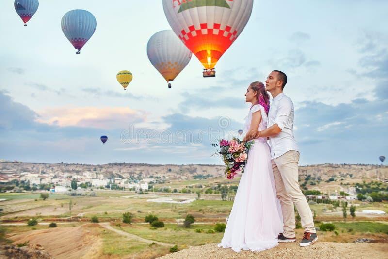 一对夫妇的日期在爱的在反对气球背景的日落在卡帕多细亚,土耳其 拥抱站立在小山的男人和妇女 免版税库存图片