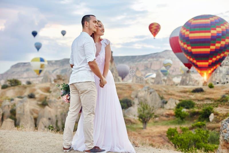 一对夫妇的日期在爱的在反对气球背景的日落在卡帕多细亚,土耳其 拥抱站立在小山的男人和妇女 免版税库存照片