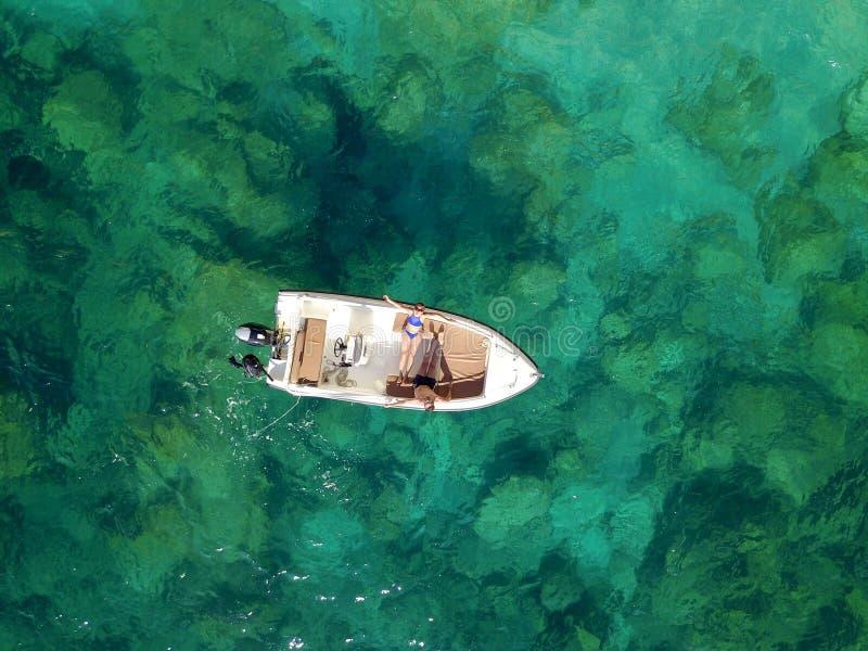一对夫妇的航测在小船的在温暖一起晒日光浴 免版税库存图片