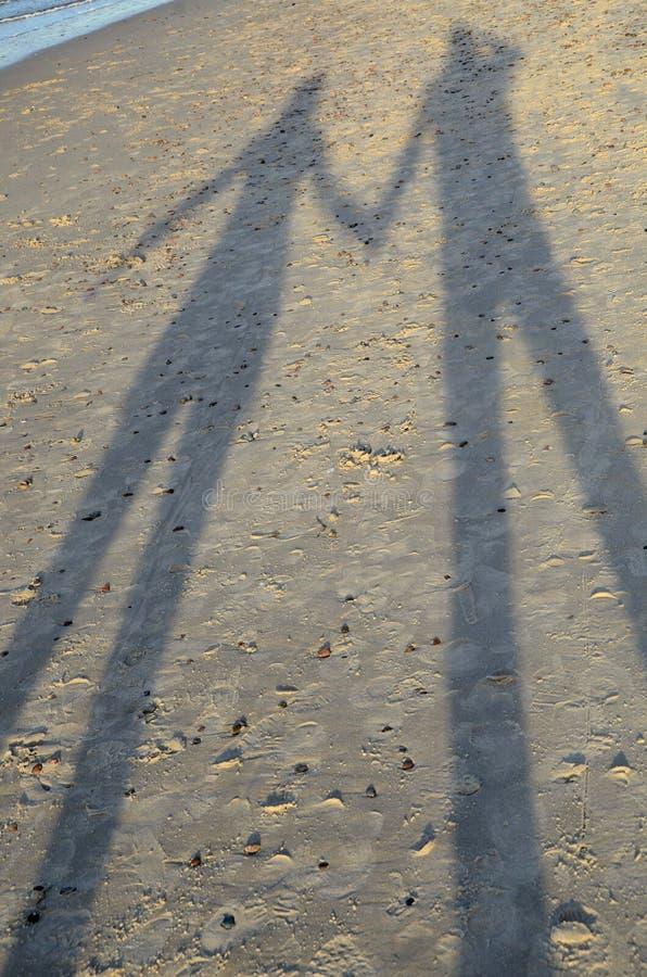 一对夫妇-恋人的阴影-在沙子 免版税库存照片