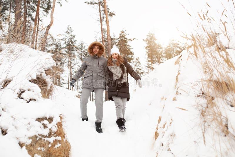 一对年轻夫妇、男人和妇女在冬天积雪的森林里走 免版税库存图片