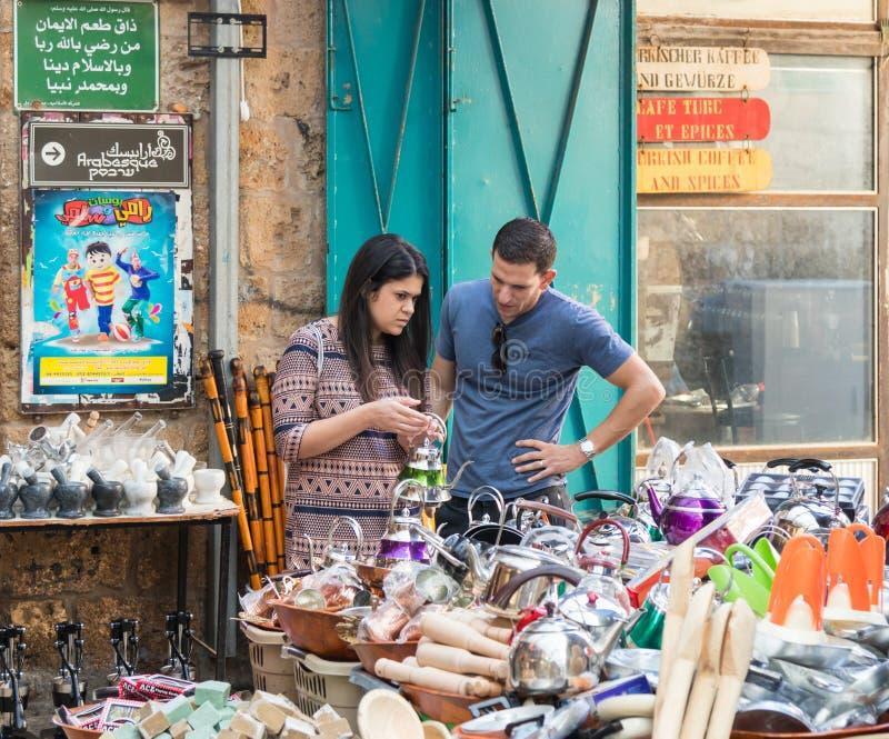 一对年轻夫妇买在一个小店的一个茶壶在市场上在老城英亩在以色列 图库摄影