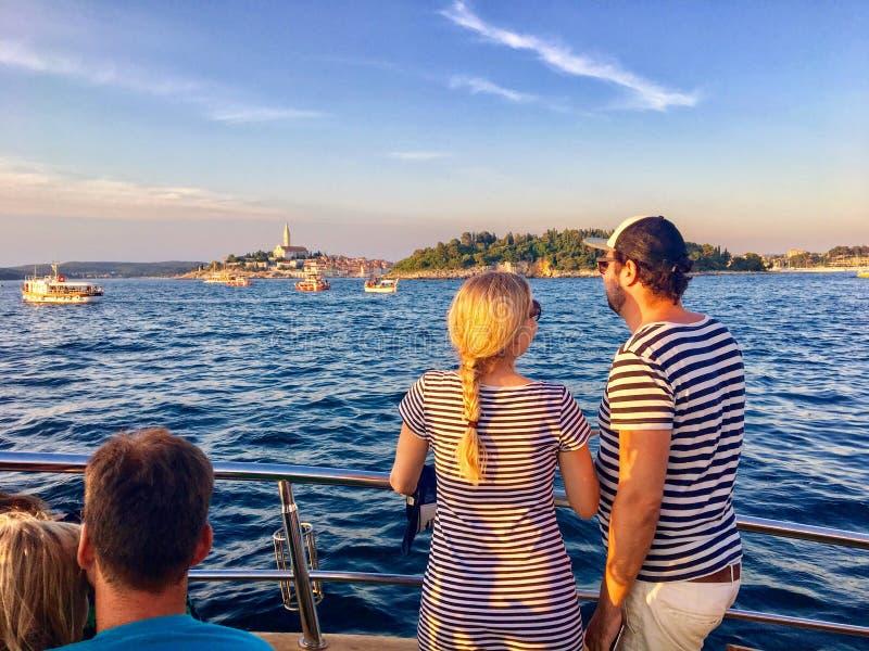 一对年轻夫妇在一次平衡的海豚观看的游览时寻找海豚在美丽的罗维尼,克罗地亚外面 免版税库存照片