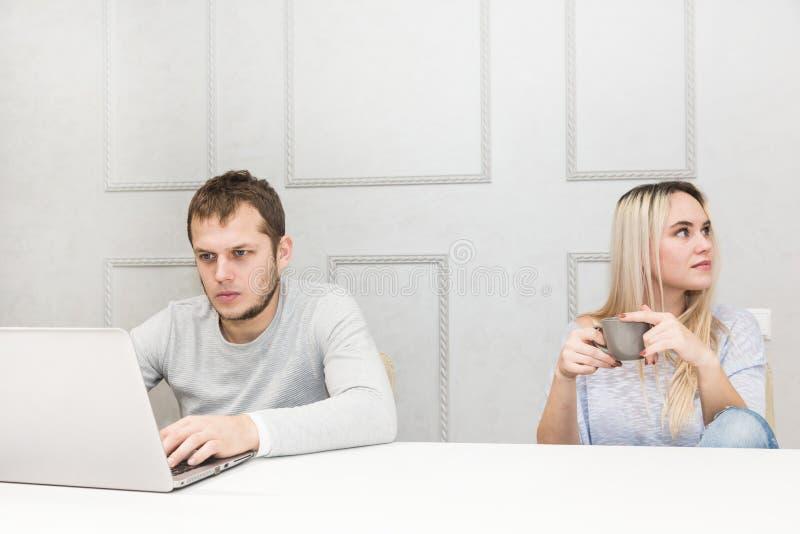 一对年轻夫妇有早餐A人在膝上型计算机后工作,妇女乏味看对边 库存图片