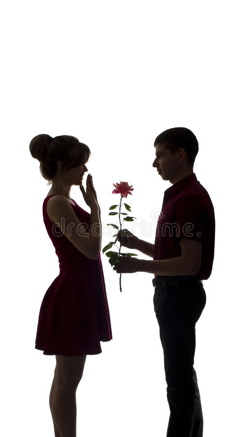 一对年轻夫妇的剪影在爱的在白色被隔绝的背景,人给妇女一朵玫瑰色花,概念爱 库存图片