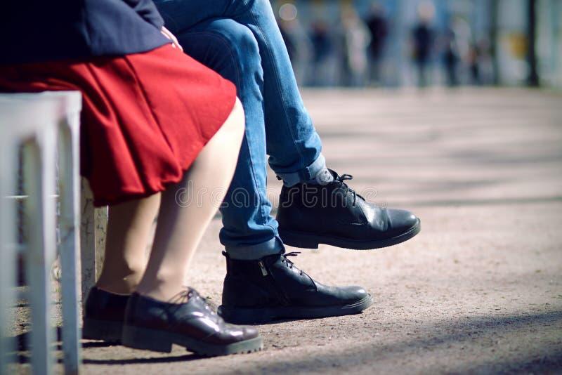 一对年轻夫妇的腿坐在长凳的一个夏日 库存照片