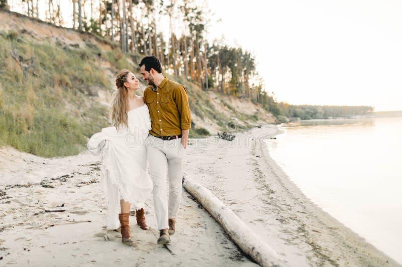 一对年轻夫妇获得乐趣并且走在海海岸线 看彼此的新婚佳偶与柔软 浪漫 免版税库存图片