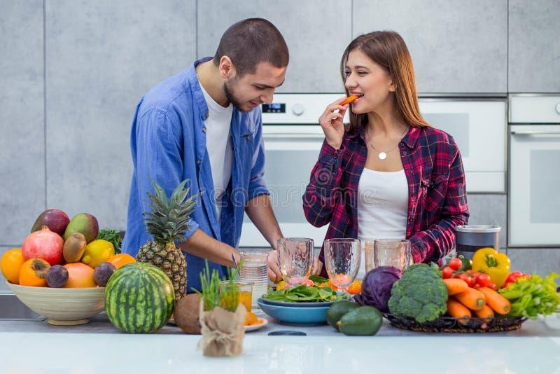 一对年轻夫妇蔬菜和水果为圆滑的人做准备,并且夫人享用红萝卜 免版税库存照片