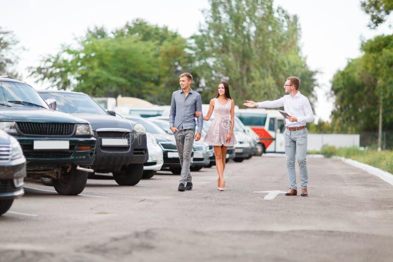 一对年轻夫妇选择一辆半新车 半新车题材 免版税库存图片
