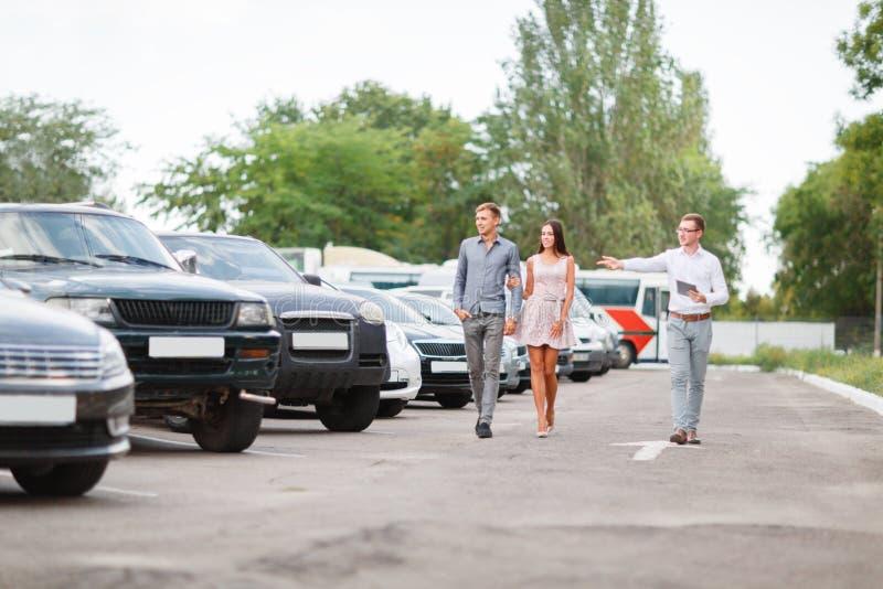 一对年轻夫妇选择一辆半新车 半新车题材 免版税库存照片
