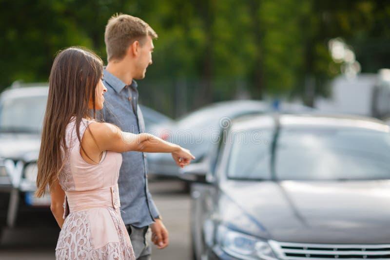 一对年轻夫妇选择他们的第一辆汽车 恋人在有蓬卡车附近走并且看汽车 Q 免版税库存照片