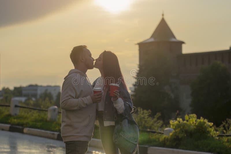 一对年轻夫妇-女孩和男孩日落夏天天空背景 人的剪影和阴影 库存图片