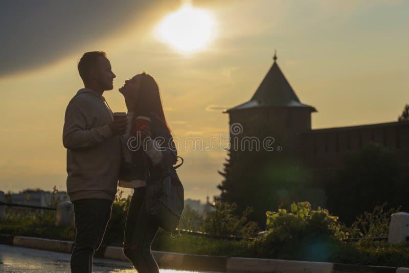 一对年轻夫妇-女孩和男孩日落夏天天空背景 人的剪影和阴影 库存照片