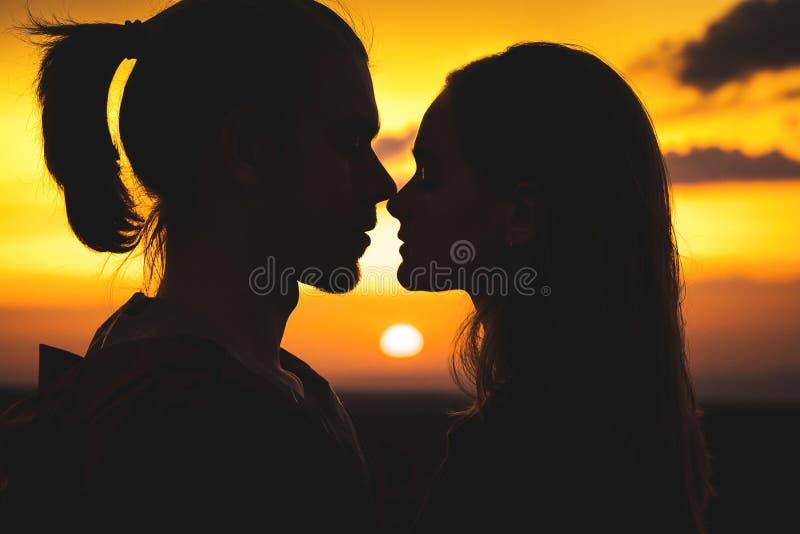 一对年轻millenial夫妇的剪影的特写镜头在准备好的爱的亲吻与人和女孩反对 免版税库存照片