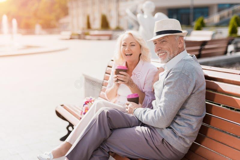 一对年长夫妇在正方形走 他们喝咖啡并且获得乐趣 免版税库存照片
