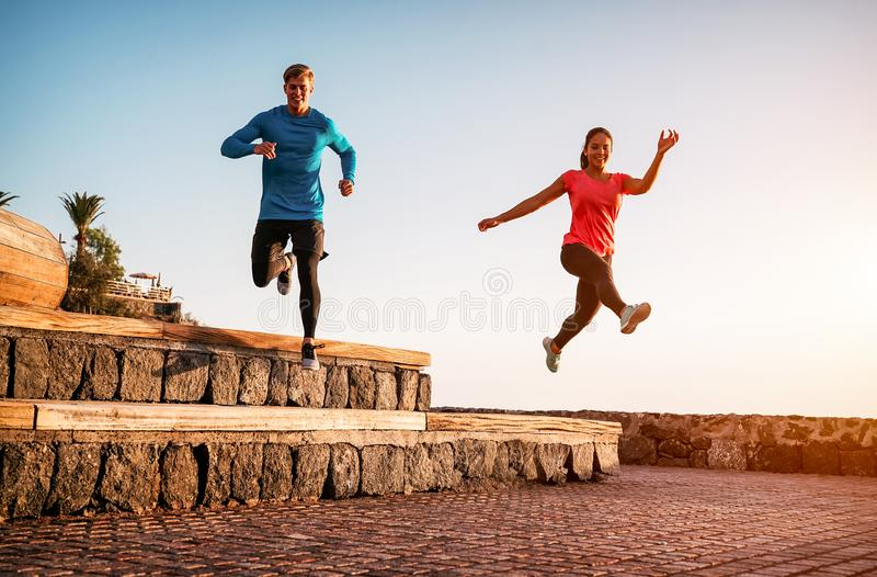 一对情侣在日落的户外锻炼跑步 — 运动型年轻人在海滩上慢跑 库存图片