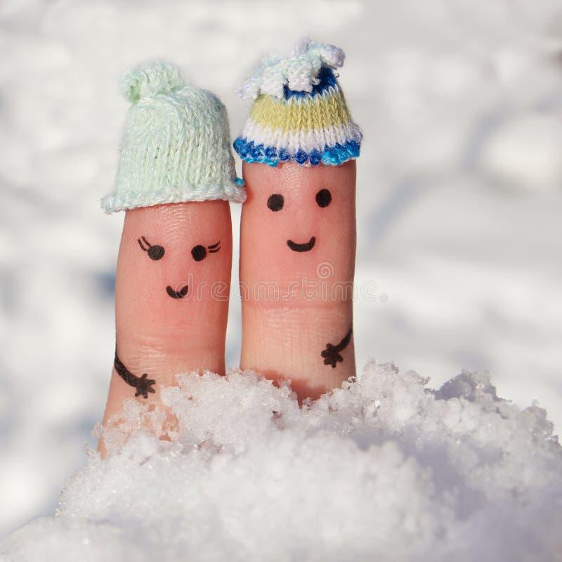 一对愉快的夫妇的手指艺术在雪背景的  免版税图库摄影