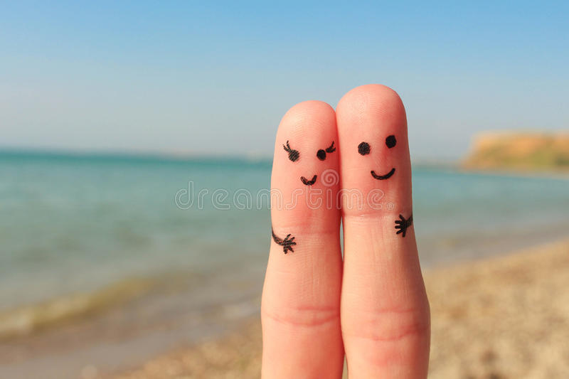 一对愉快的夫妇的手指艺术 男人和妇女有海滩海的一基于 男人和妇女在背景海拥抱 免版税库存照片