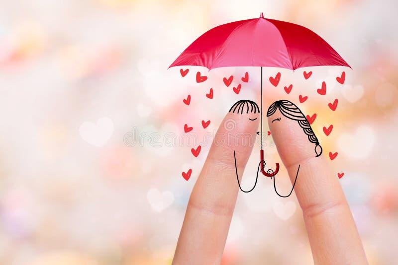 一对愉快的夫妇的概念性手指艺术 恋人亲吻在伞下 图象纵向股票妇女年轻人 免版税图库摄影
