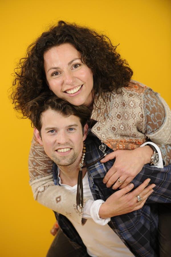 一对愉快的夫妇的画象在黄色背景的 免版税库存照片