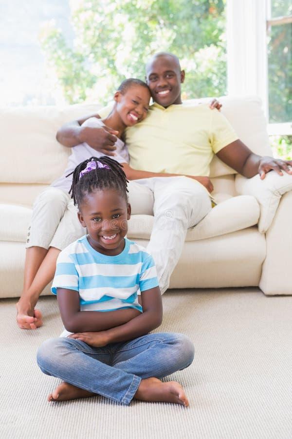 一对愉快的夫妇的画象坐couh和他们的坐和看照相机的女儿 免版税图库摄影