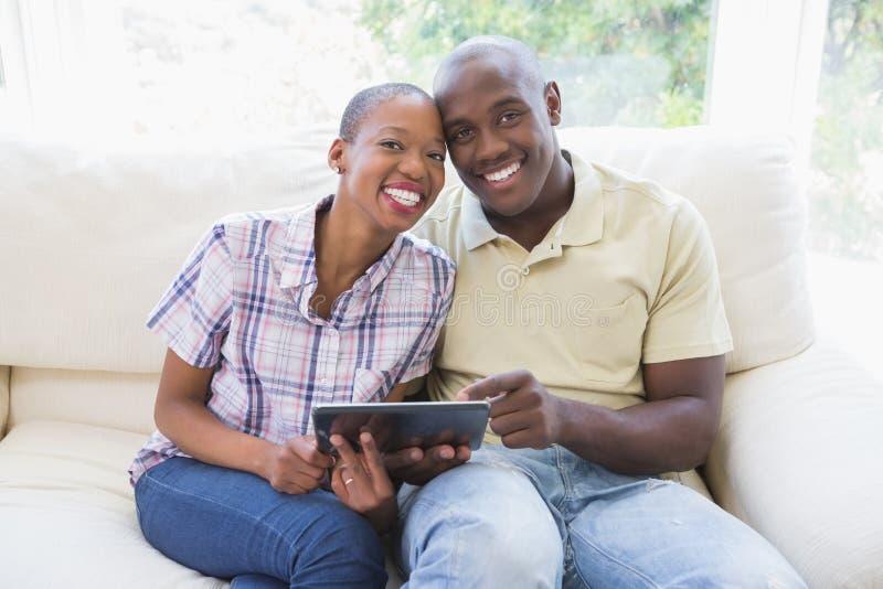 一对愉快的微笑的夫妇的画象使用数字式片剂的 免版税图库摄影