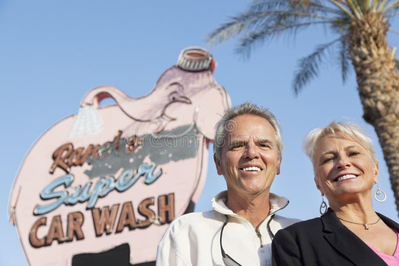 一对愉快的成熟夫妇的画象在洗车牌前面的 免版税库存图片