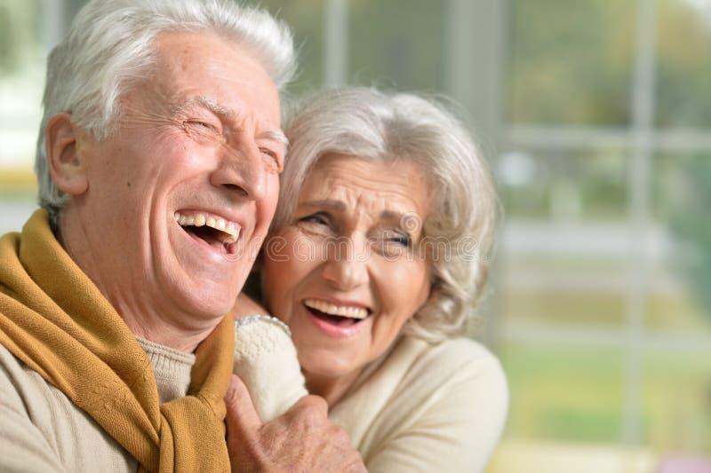 一对愉快的笑的资深夫妇的画象在家 免版税库存图片