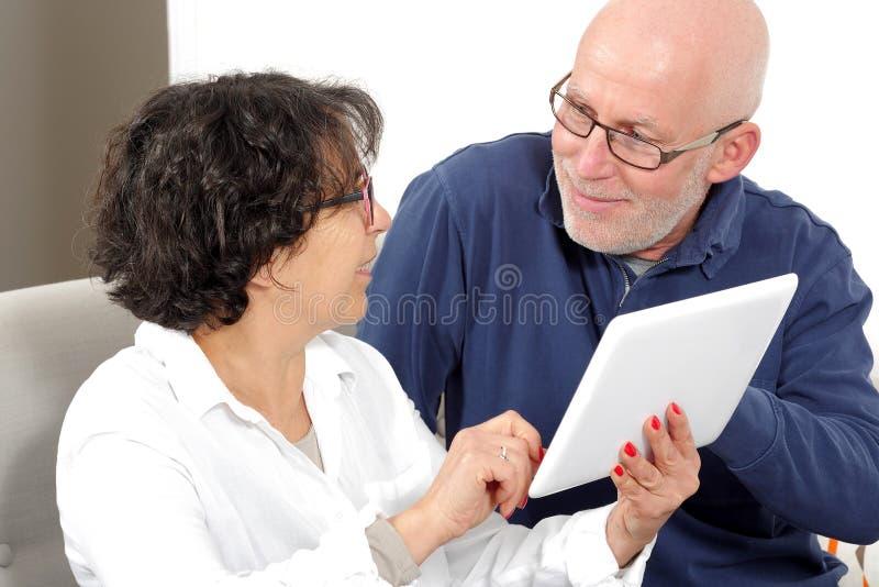 一对愉快的资深夫妇的画象使用数字式片剂的 免版税库存图片
