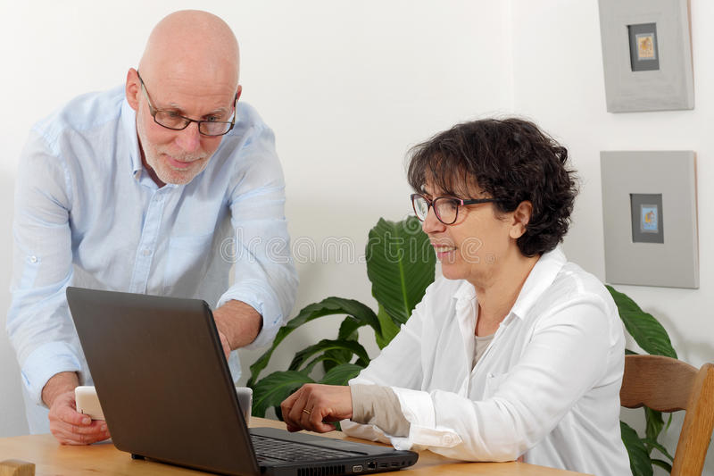 一对愉快的资深夫妇的画象使用膝上型计算机的 库存照片