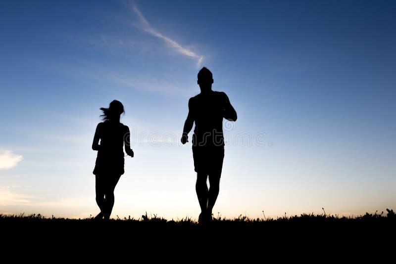 一对慢跑者夫妇的剪影在日出的 免版税库存图片