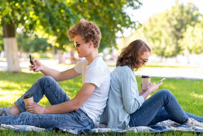 一对新夫妇 夏天本质上 有基于格子花呢披肩的女孩的一个男孩 举行热的咖啡或茶 他们看 免版税图库摄影