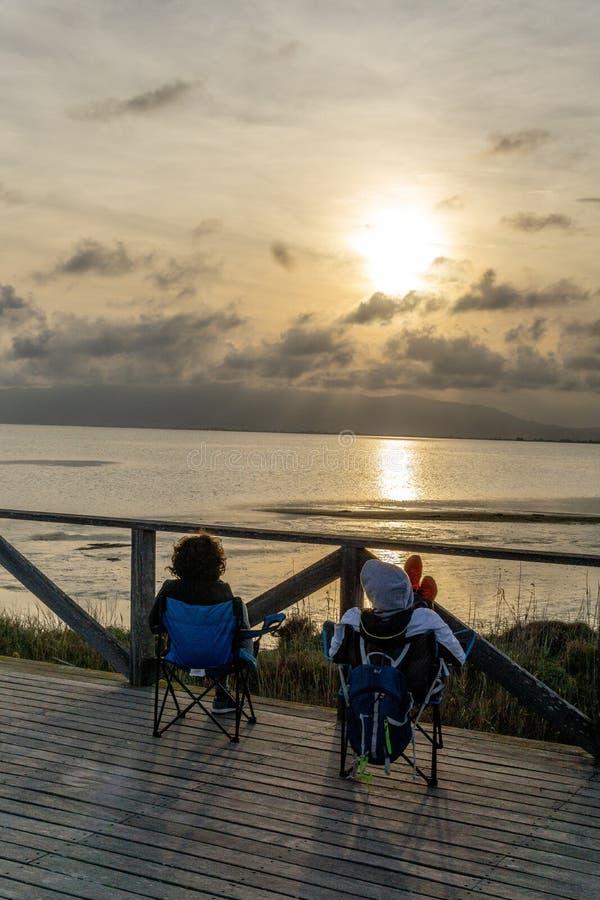 一对无法认出的夫妇冥想日落坐海 图库摄影