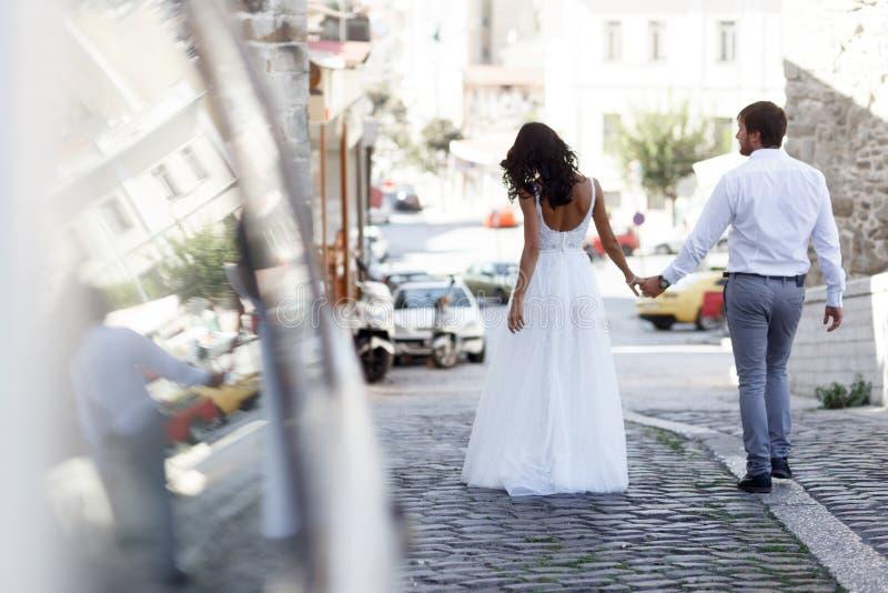 一对浪漫夫妇的后面看法在老街道希腊上的新婚佳偶步行 E 免版税库存图片