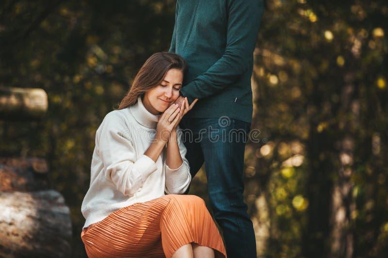 一对爱在户外的情侣站在美丽的森林里,手握女友的脸 免版税库存照片
