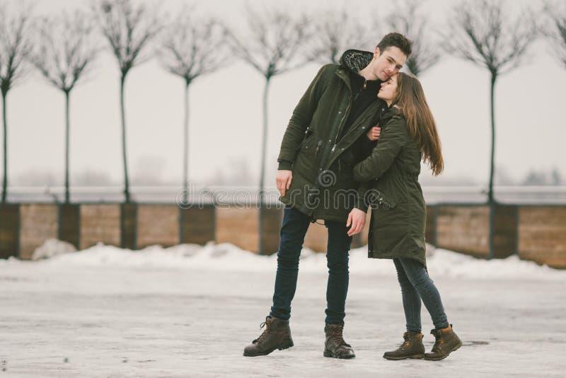 一对爱学生的异性爱夫妇年轻人男人和一名白种人妇女 在冬天,在用冰报道的城市广场, 免版税库存图片