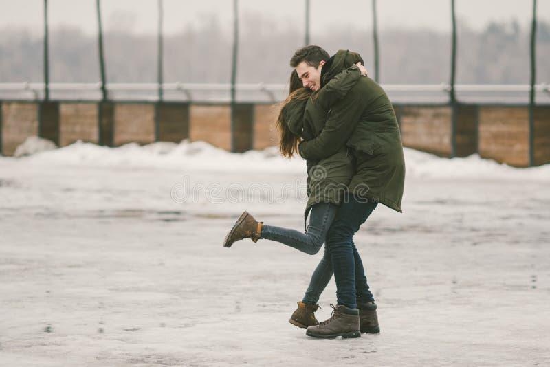 一对爱学生的异性爱夫妇年轻人男人和一名白种人妇女 在冬天,在用冰报道的城市广场, 免版税图库摄影