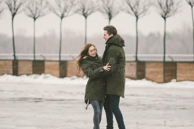 一对爱学生的异性爱夫妇年轻人男人和一名白种人妇女 在冬天,在用冰报道的城市广场, 库存图片