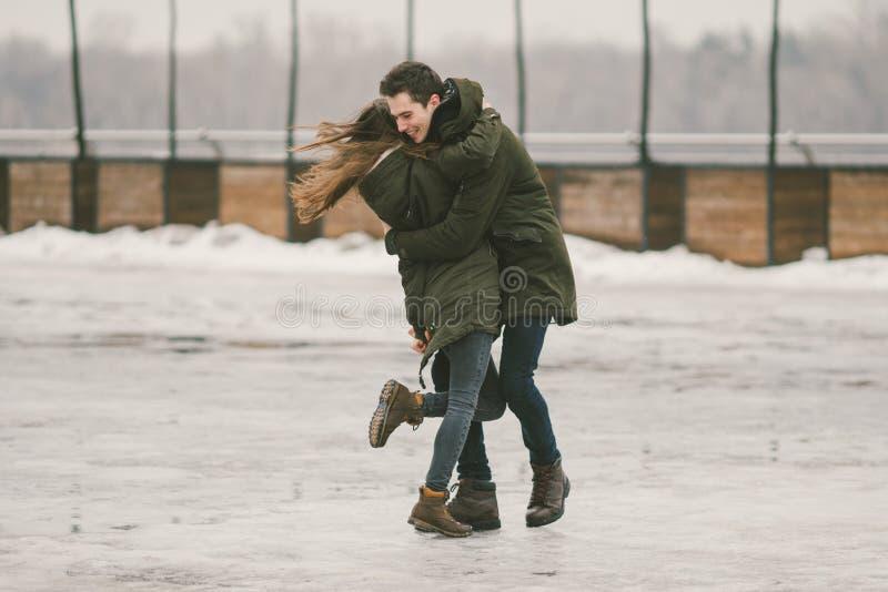 一对爱学生的异性爱夫妇年轻人男人和一名白种人妇女 在冬天,在用冰报道的城市广场, 图库摄影