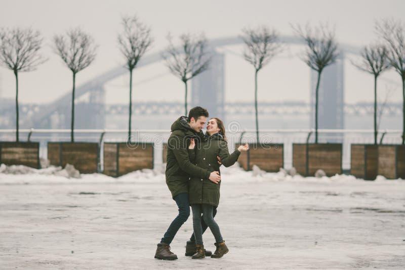 一对爱学生的异性爱夫妇年轻人男人和一名白种人妇女 在冬天,在用冰报道的城市广场, 免版税库存照片