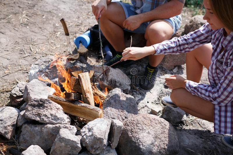 一对爱恋的夫妇在森林里助长在一顿野餐的火油煎肉 女孩点燃火本质上 新的成人 免版税图库摄影