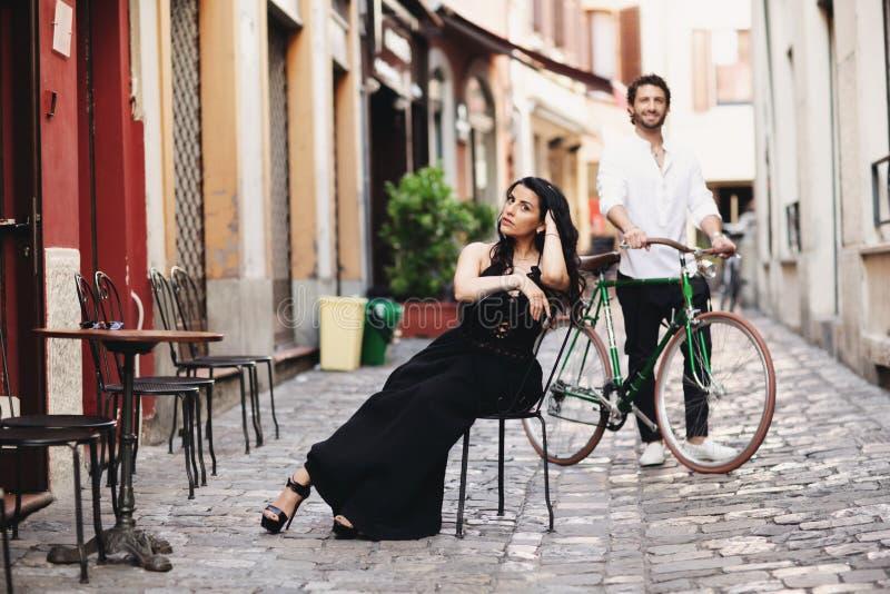 一对爱恋的夫妇在老城市 一件黑礼服的一名妇女坐椅子 在她的立场后的人与一辆绿色自行车 免版税库存照片