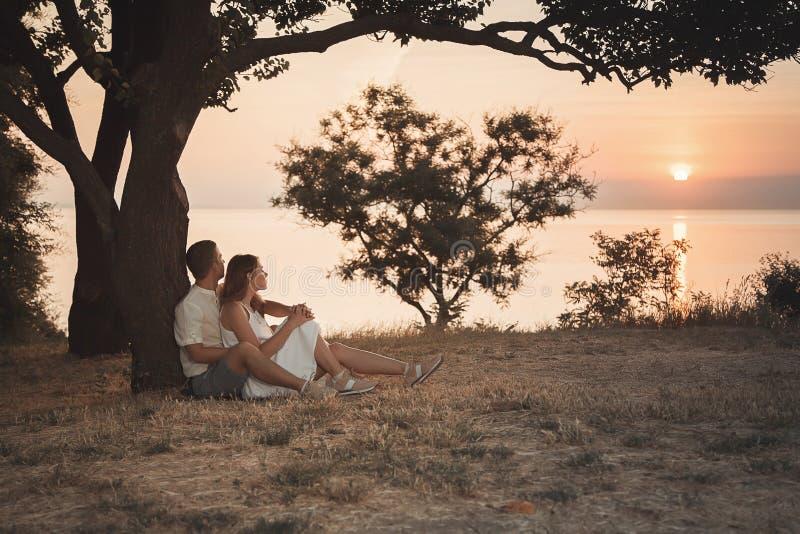 一对爱恋的夫妇坐拥抱在树下 免版税库存图片