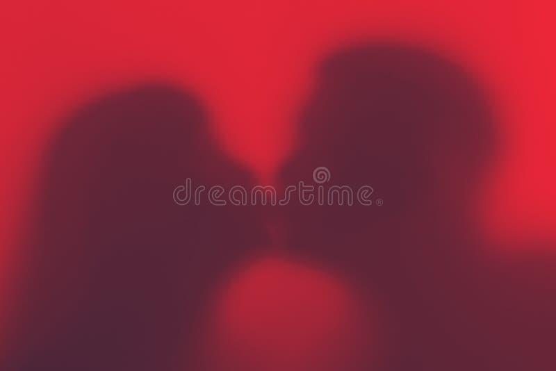 一对爱恋的夫妇的剪影在亲吻期间的 恋人剪影 免版税库存图片