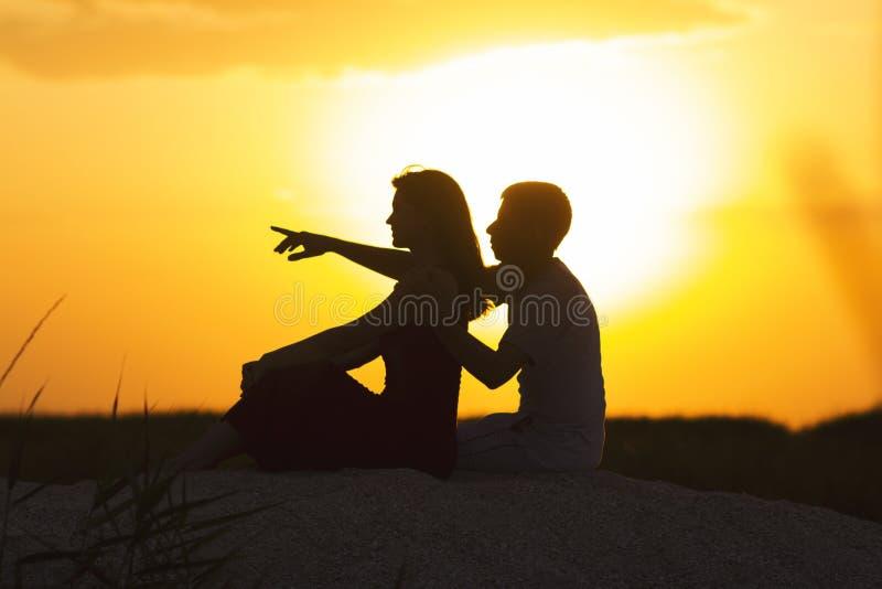 一对爱恋的夫妇的剪影在日落的坐在海滩的沙子,一个人的图和爱的一名妇女,一个浪漫场面  免版税图库摄影
