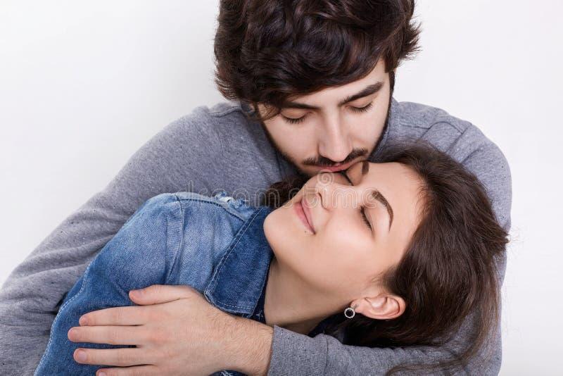 一对爱恋的夫妇被隔绝在白色背景 拥抱和亲吻他的女朋友的一个年轻人 yo之间的肉欲的关系 图库摄影