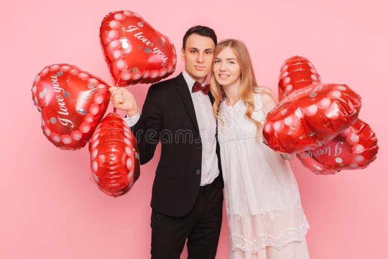 一对爱恋的夫妇,男人和妇女,拿着心形的气球,在桃红色背景的一个演播室,概念为情人节 免版税图库摄影