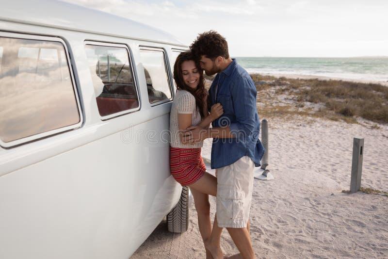 一对白种人夫妇的侧视图在露营者货车倾斜了,当拥抱的他们反对海洋i时 库存照片